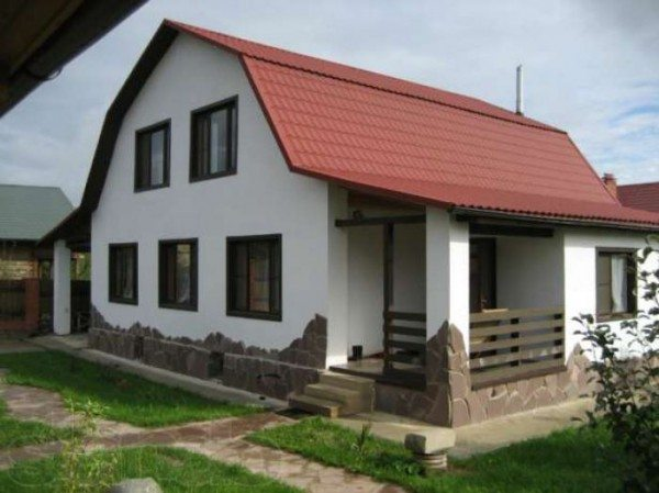 Применение волнистого оформления фундамента оживило общий рисунок дома.