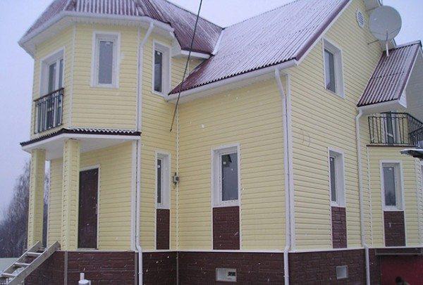 Фасад желтого цвета с темными элементами.