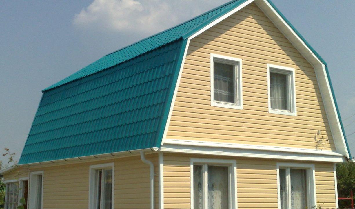 Необычный дизайн небольшого домика под голубой черепицей, обшитого светлым виниловым блок хаусом